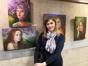 Svetlana Belova against the background of her work at the exhibition of paintings